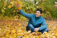 siiting在秋天叶子的愉快的人在公园 免版税图库摄影