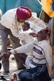 Sikh dentist treats teeth of old man without during traditional camel fair holiday at Pushkar,India stock photo