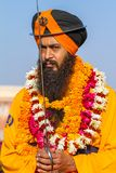 Sikh devotee with orange turban and flowers Royalty Free Stock Image
