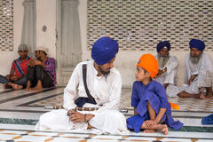 Sikh man and boy visiting the Golden Temple in Amritsar, Punjab, India. AMRITSAR, INDIA - SEPTEMBER 27, 2014: Unidentified Sikh man and boy visiting the Golden Stock Image