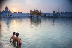 Sikh men bath in the holy lake at Golden Temple Stock Image