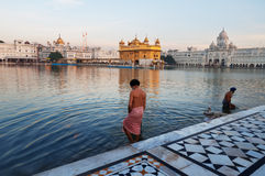 Sikh men bath in the holy lake at Golden Temple in the early morning. Amritsar. India Stock Photos