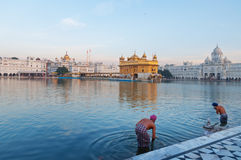 Sikh men bath in the holy lake at Golden Temple in the early morning. Amritsar. India Stock Image