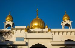 Sikh temple golden domes gleam in the sun. On the roof in Makindu, Kenya. Sikhism religion. Guru Singh royalty free stock photos