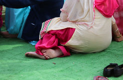 Sikh woman with bare feet during the ceremony Stock Photo