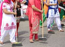 Sikh women while scavenging the street with a broom during a fes Royalty Free Stock Images