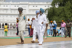 Sikhs and indian people visiting the Golden Temple in Amritsar, Punjab, India. AMRITSAR, INDIA - SEPTEMBER 26, 2014: Unidentified Sikhs and indian people Royalty Free Stock Image