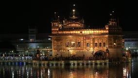 Sikhs y gente india que visitan el templo de oro en Amritsar en la noche La India almacen de video