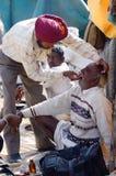 Sikhzahnarzt behandelt Zähne des alten Mannes außen während des angemessenen Feiertags des traditionellen Kamels bei Pushkar, Ind Stockfoto
