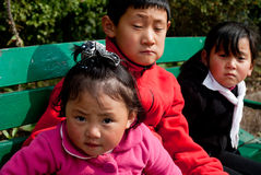 Sikkimies Children. Three Sikkimies children are enjoying the sunny day by sitting in a bench of a Tibet museum in Gangtok, Sikkim, India Royalty Free Stock Photography