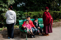 Sikkimies Children. Three Sikkimies children are enjoying the sunny day by sitting in a bench of a Tibet museum in Gangtok, Sikkim, India Royalty Free Stock Image