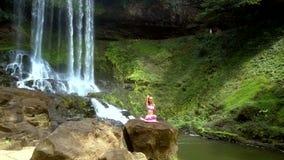 Siklawa biega zmniejszający się w rzekę i dziewczynę na kamieniu zbiory