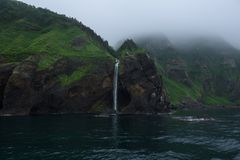 Siklawa zrzut od wysokich skalistych falez w oceanu morze Okhotsk wokoło Shiretoko półwysepa Obraz Royalty Free