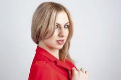 Sikt åt sidan av den unga kvinnan i rött omslag Arkivbild