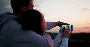 Sikt över att älska parskuldran De ser fotona var de är kyssande lager videofilmer