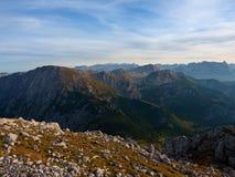 Sikt över den alpina klippan och dalen Solen på horisonten, blå himmel med få fördunklar sikt för alpshochriesberg Royaltyfri Bild