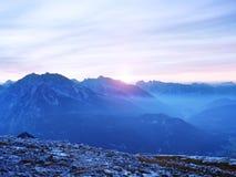 Sikt över den alpina klippan och dalen Solen på horisonten, blå himmel med få fördunklar sikt för alpshochriesberg Arkivfoton