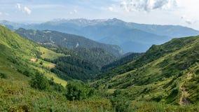 Sikt över den gröna dalen som omges av bergvyskokimi på en klar sommardag Krasnaya Polyana, Sochi, Kaukasus, Ryssland arkivfoto