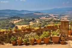 Sikt över det Tuscany landskapet med krukor av blommor längs Balusen Royaltyfri Foto