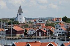 Sikt över en liten svensk by och en kyrka med en le framsida arkivbild