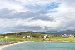 Sikt över en norsk fjord till en ö med fiskekojor och r arkivbilder