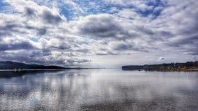 Sikt över en sjö med himmelreflexion Arkivbilder