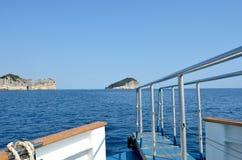 Sikt över enplanka in mot två steniga öar arkivfoto