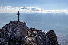 Sikt över ett bergmaximum med ett toppmötekors ner till Innvalleyen och Innsbrucken i Österrike i höst som sett från a via Ferrat royaltyfri bild