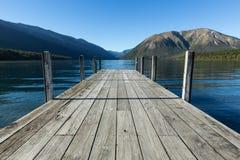 Sikt över sjön in mot berg från den gråa pir Royaltyfria Bilder
