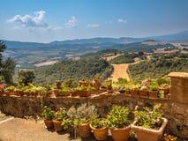 Sikt över Tuscany Hilly Landscape med krukor av blommor längs Royaltyfri Bild