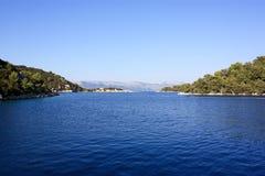 Sikt över vatten som ser in mot backar Arkivfoto