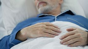 Sikt av överansträngde rynkiga händer av den kloka gamala mannen som somnar fridfullt i säng Royaltyfria Bilder