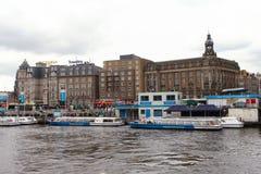 Sikt av Amsterdam från central byggnad för drevstation med en kanal Arkivbilder