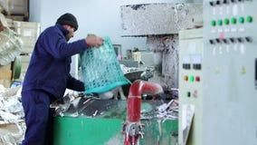 Sikt av arbetaren som arbetar i pappers- återvinningfabrik lager videofilmer