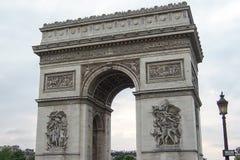 Sikt av Arcet de Triomphe i mitten av Paris den molniga molniga våraftonen royaltyfri foto