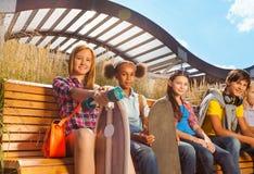Sikt av barn som sitter på träbänk tillsammans Arkivbilder