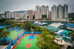 Sikt av basketdomstolar på Ap Lei Chau och skyskrapor i Aber Royaltyfria Bilder