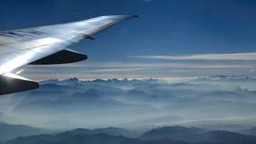 Sikt av berg och dalen från flygplanfönster arkivbilder