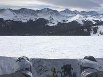 Sikt av bergen i avståndet över en snowboard Royaltyfri Foto