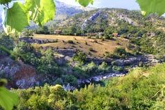 Sikt av bergfloden som övervinner steniga kuster och stenforsar bland bygden i bergen av Montenegro royaltyfria foton