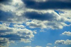 Sikt av blå himmel för vår med moln som är upplysta vid solen Arkivfoton