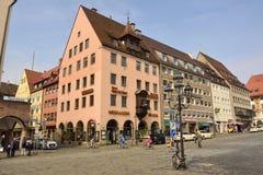 Sikt av bostads- och kommersiella byggnader på genomskärningen av den Hauptmarkt fyrkanten och den Tuchgasse gatan i Nuremberg Royaltyfri Foto