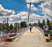 Sikt av bron över floden Tammerkoski (Finland, Tammerfors), med fartyg på floden och folket som går över en br royaltyfri fotografi