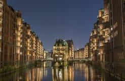 Sikt av bron och tegelstenbyggnaden i Hamburg, nattillu arkivbild