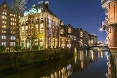 Sikt av bron och tegelstenbyggnaden i Hamburg, nattillu arkivbilder