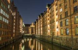 Sikt av bron och tegelstenbyggnaden i Hamburg, nattillu royaltyfri foto