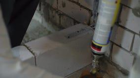 Sikt av byggmästarehänder genom att använda montera skum för att fylla tomt utrymme mellan väggar lager videofilmer