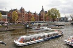 Sikt av byggnad för Amsterdam central drevstation med en kanal Arkivfoto
