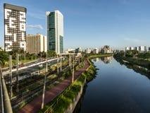 Sikt av byggnader, CPTM-drevet, trafik av medel och floden i marginell Pinheiros flodaveny royaltyfria foton