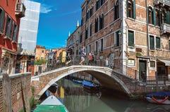 Sikt av byggnader och bron framme av en kanal på Venedig Fotografering för Bildbyråer